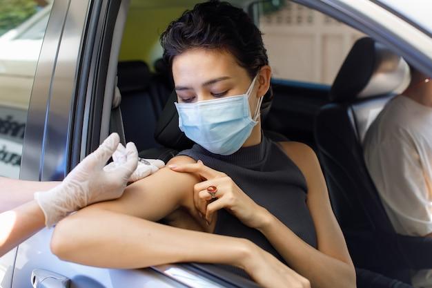 Foto de closeup retrato de paciente do sexo feminino sentar na fila do drive thru olhar no ponto da câmera e receber injeção de vacina de coronavírus, tiro no ombro da seringa na mão do médico usa luvas de borracha.