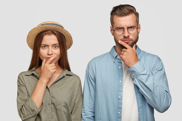 Foto de colegas de trabalho confusos, do sexo feminino e masculino, mantendo as mãos no queixo