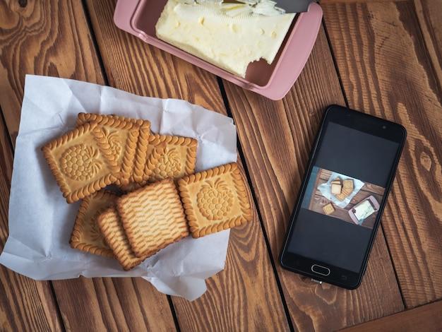 Foto de comida tirada no telefone por um blogueiro de culinária cookies em uma bandeja de madeira para uma foto no telefone