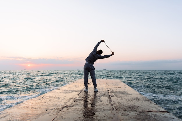 Foto de comprimento total de desportista praticando exercícios, alongamento com pular corda