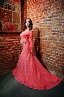Foto de comprimento total de garota modelo elegante no vestido rosa com parede de tijolos.