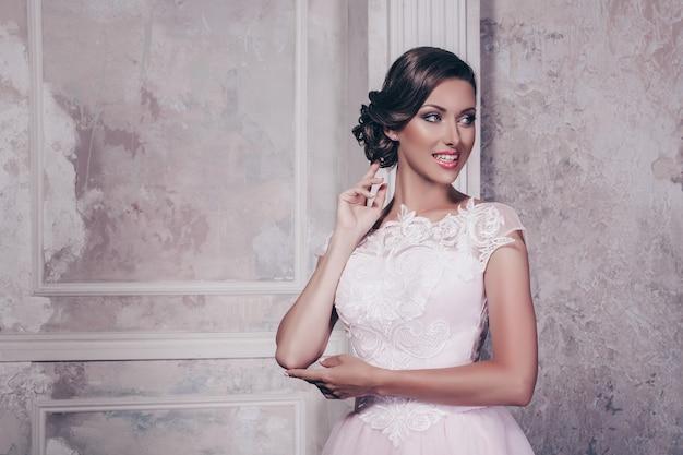 Foto de comprimento total de linda mulher magro, com longos cabelos ondulados, posando em casual vestido branco e salto alto preto, segurando o braço no quadril