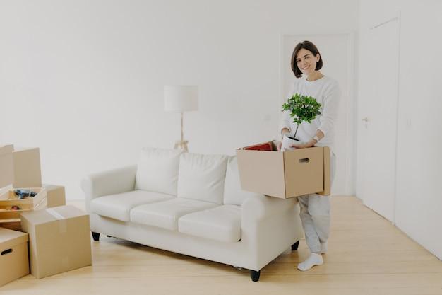 Foto de comprimento total de mulher morena alegre mantém caixa de papelão com planta interna