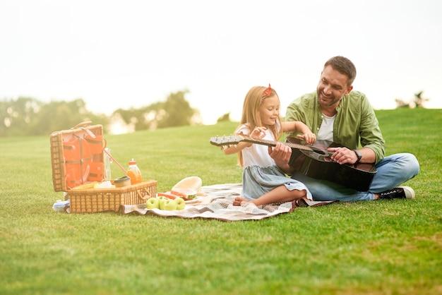Foto de comprimento total de uma menina feliz sentada com seu pai amoroso em uma grama verde no parque e