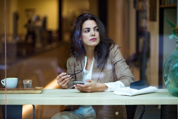 Foto de concentrada jovem empresária enviando mensagens de texto com seu celular na cafeteria.