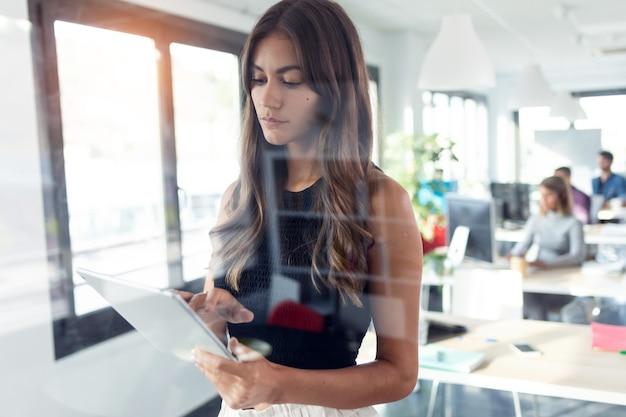 Foto de concentrada jovem empresária usando seu tablet digital em pé no escritório de inicialização moderna.
