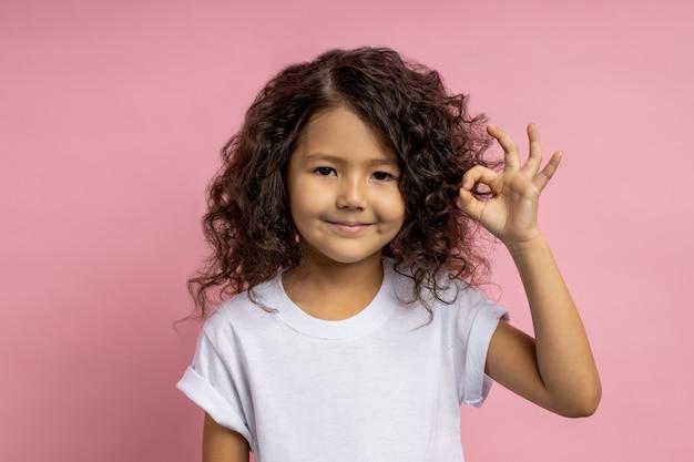 Foto de confiante linda garotinha caucasiana com cabelo escuro encaracolado, em uma camiseta branca, levantando a mão e dando um sinal de ok, expressando aprovação. gesto, linguagem corporal.