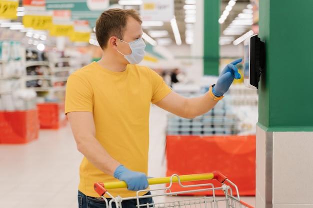 Foto de consumidor masculino usa touchscreen na loja, verifica o preço, posa com carrinho de compras, usa luvas e máscara descartável
