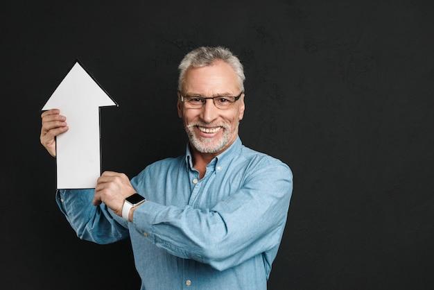 Foto de conteúdo homem idoso de 60 anos com barba e cabelos grisalhos, segurando o ponteiro de seta em branco discurso direcionando para cima, isolado sobre a parede preta