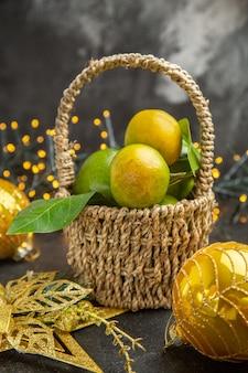 Foto de cor de fundo escuro com maçãs verdes frescas com tangerinas e frutas do feriado de natal vista frontal