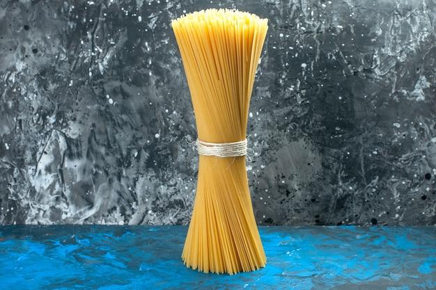 Foto de cor de massa italiana longa de massa crua amarrada em refeição de luz azul