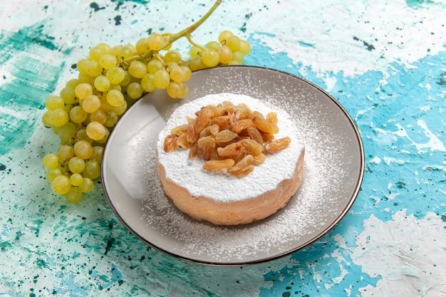Foto de cor de passas secas de uva com uvas verdes frescas e bolo de açúcar em pó na superfície azul claro
