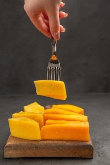 Foto de cor escura com queijo fresco fatiado no garfo café da manhã refeição lanche