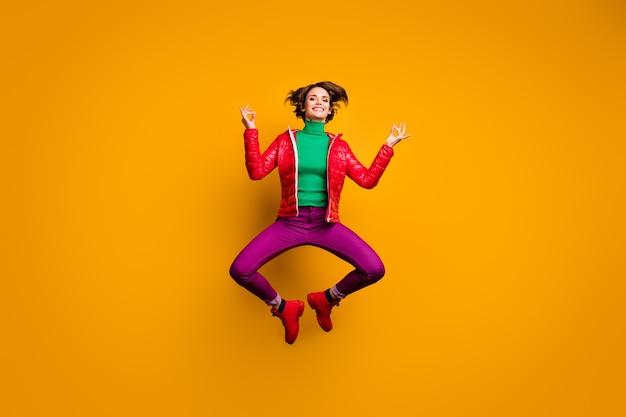 Foto de corpo inteiro, cabelo castanho funky boob menina desportiva salto exercício ioga vestir roupa vermelha roxa botas look moderno suéter verde primavera elegante