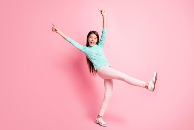 Foto de corpo inteiro da fofa linda hispânica, penteado longo, dança, levante as mãos para cima, dedos diretos, use calça de moletom turquesa, tênis branco isolado fundo de cor rosa
