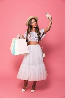 Foto de corpo inteiro da moda mulher usando chapéu de palha e saia fofa segurando sacolas de papel colorido e tomando selfie em smartphone