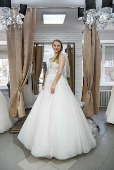 Foto de corpo inteiro da noiva na loja de casamentos