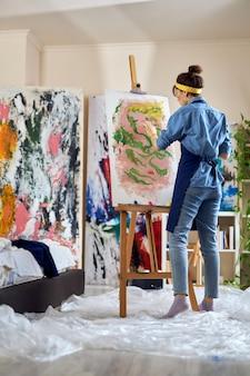Foto de corpo inteiro da talentosa artista feminina pintando avental sobre tela em uma oficina de estúdio caseiro