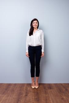 Foto de corpo inteiro da vista frontal de uma jovem empresária confiante no espaço cinza