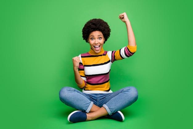 Foto de corpo inteiro de alegre encantada garota afro-americana de sorte sentar pernas cruzadas dobradas ganhar loteria levantar punhos gritar sim usar roupa bonita