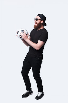 Foto de corpo inteiro de alegre jovem barbudo segurando bola de futebol e sorrindo sobre branco