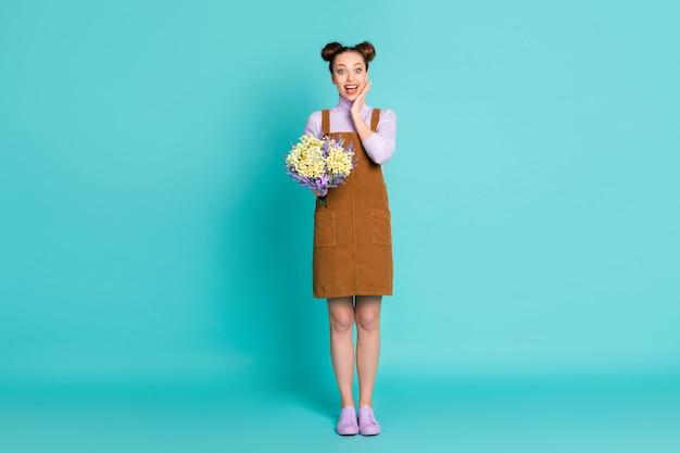Foto de corpo inteiro de atraente muito fofo alegre animado dois pãezinhos penteado namorada senhora namorado flores para presente inesperado b-dia palma queixo usar roupa de outono isolado azul-petróleo cor de fundo