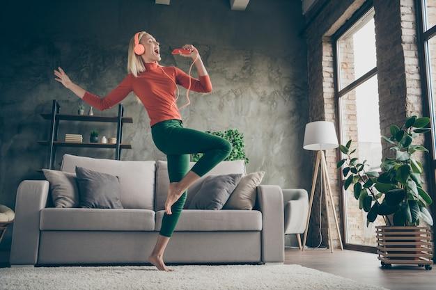 Foto de corpo inteiro de baixo ângulo de visão de uma senhora bonita segurando um telefone ouvindo música modernos fones de ouvido laranja dançando cantando alto, use roupa casual sala de estar