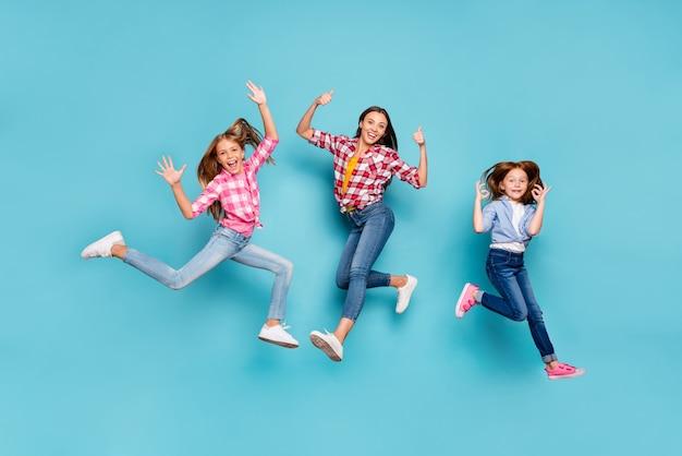 Foto de corpo inteiro de branco regozijando-se com a família vencedora, tendo dado feedback sobre algo vestindo jeans enquanto isolado com fundo azul