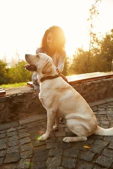Foto de corpo inteiro de cachorro branco bonito com proprietário no parque andando