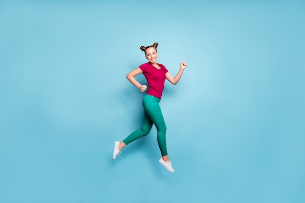 Foto de corpo inteiro de corpo inteiro de alegre garota de perfil positivo vestindo uma camiseta vermelha sorrindo com os dentes correndo para as vendas pulando em calças verde isolado azul pastel parede