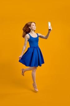 Foto de corpo inteiro de corpo inteiro de mulher ruiva na moda elegante tomando selfie pulando em fundo amarelo estúdio isolado de vestido azul, retrato. copie o espaço