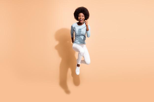 Foto de corpo inteiro de corpo inteiro de uma garota esportiva energética de pele escura pulando alto, correndo rápido gritando bem alto, isolada em um fundo de cor bege