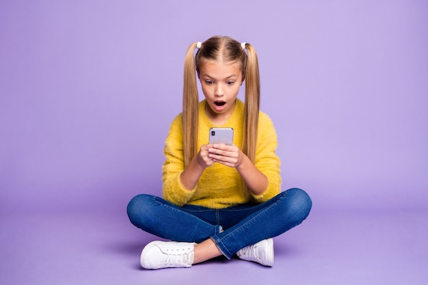 Foto de corpo inteiro de criança impressionada sente-se com as pernas cruzadas e cruzadas, use o smartphone, leia a rede social, notificação grite, omg uau, use tênis pullover amarelo parede de cor roxa isolada
