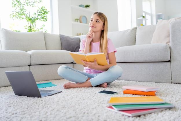 Foto de corpo inteiro de criança ocupada, menina sentada no chão, tapete, pernas cruzadas, dobradas, ler livro, tocar o queixo, mão, pensar, analisar informações, estudar, remoto, em casa, dentro