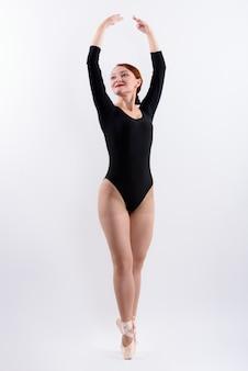 Foto de corpo inteiro de dançarina de balé na ponta dos pés isolada contra um fundo branco