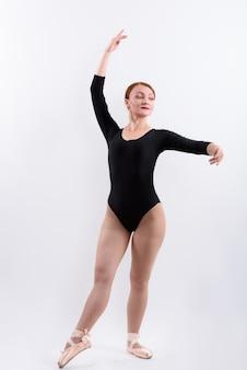 Foto de corpo inteiro de dançarina de balé pronta para dançar, isolada contra um fundo branco