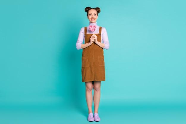 Foto de corpo inteiro de dois pãezinhos penteados senhora pessoa braços segurar em forma de coração saboroso bastão doce desgaste outono mini vestido marrom violeta calçado pulôver isolado turquesa cor de fundo