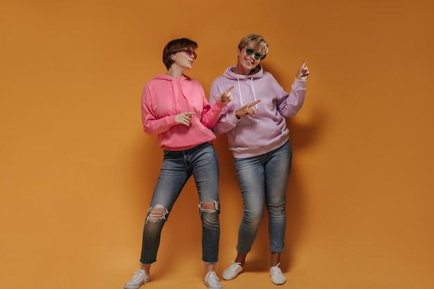 Foto de corpo inteiro de duas mulheres com cabelo curto em óculos de sol brilhantes, capuz lilás e rosa e jeans mostrando para colocar para texto em fundo laranja.