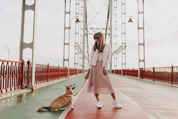Foto de corpo inteiro de elegante mulher europeia vestindo saia rosa e jaqueta branca, andando com um cachorro corgi na cidade ensolarada de manhã.