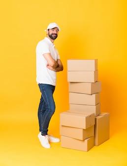 Foto de corpo inteiro de entregador entre caixas sobre amarelo isolado com os braços cruzados e olhando para a frente