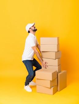 Foto de corpo inteiro de entregador entre caixas sobre amarelo