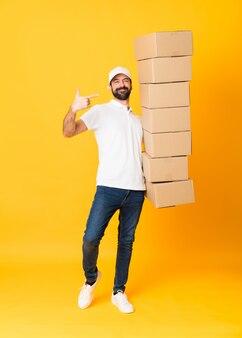 Foto de corpo inteiro de entregador entre caixas