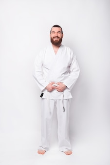 Foto de corpo inteiro de esportista em uniforme de taekwondo em pé sobre uma parede branca
