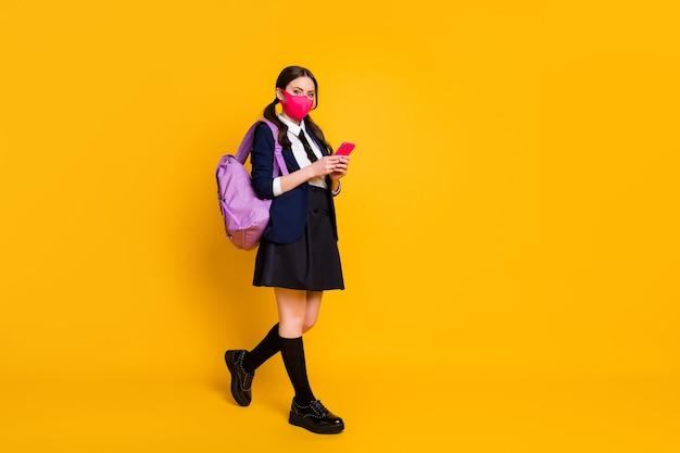 Foto de corpo inteiro de estudante universitária usando celular e máscara de uniforme escolar