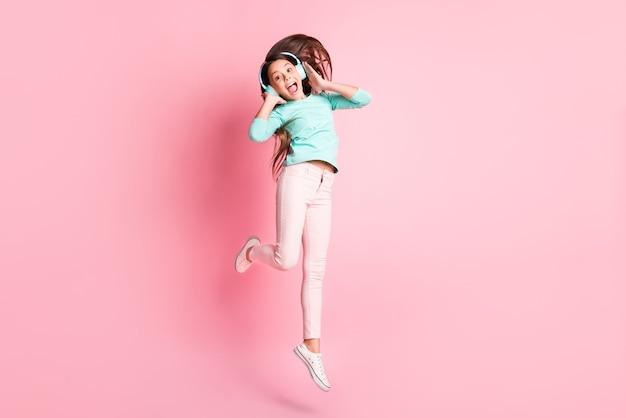 Foto de corpo inteiro de fofa doce pequena funky louca senhora latina pular boca aberta mãos orelhas usar fones de ouvido turquesa calça moletom tênis branco isolado fundo de cor rosa