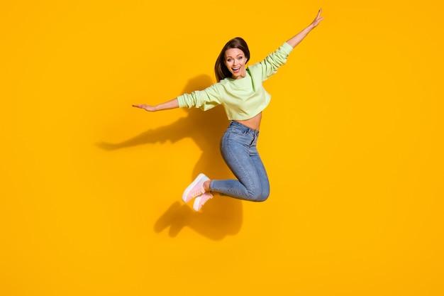 Foto de corpo inteiro de garota energética descuidada pulando, segurando a mão, aproveitando a mosca