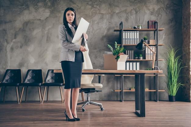 Foto de corpo inteiro de garota estressada frustrada, agente de marketing, não quer sair do emprego, escritório, segurar a tela do computador, usar uma jaqueta blazer de salto alto na estação de trabalho
