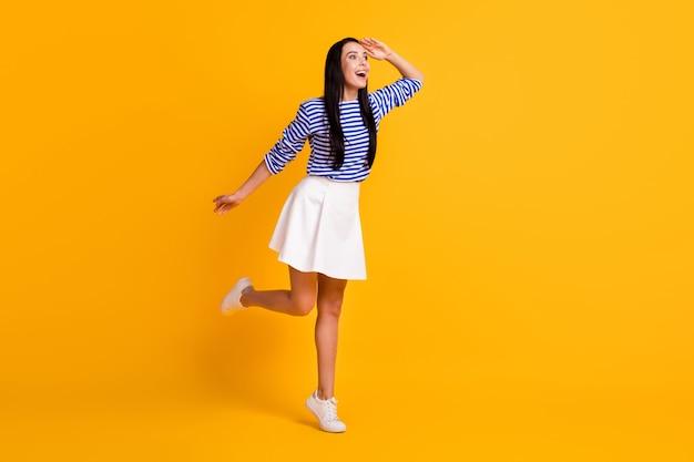 Foto de corpo inteiro de garota positiva surpresa, segurando a mão, olhar copyspace ver para a frente descontos incríveis em vendas usar roupa estilo sapatos esportivos isolados sobre um fundo de cor vívida