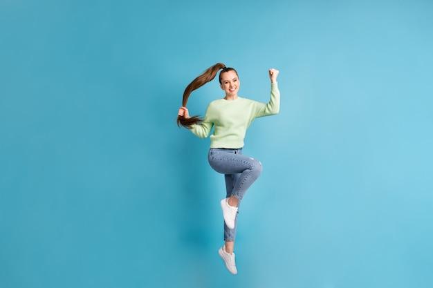 Foto de corpo inteiro de garota pulando com rabo de cavalo comprido gesticulando como o vencedor isolado em um fundo de cor azul brilhante