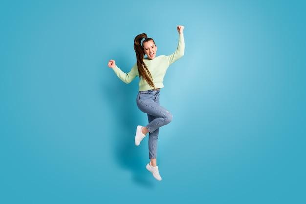 Foto de corpo inteiro de garota pulando com rabo de cavalo gesticulando como o vencedor gritando isolado em um fundo de cor azul vibrante